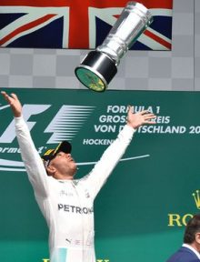Lewis Hamilton throws up the trophy in celebration after winning in Germany. Photo: Thomas Kienzle/AFP/Getty Images