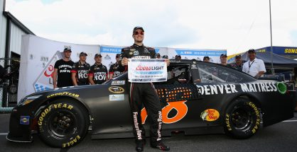 Martin Truex Jr. poses for pictures in front of his car after winning the pole at Pocono. Photo: Adam Glanzman/Getty Images