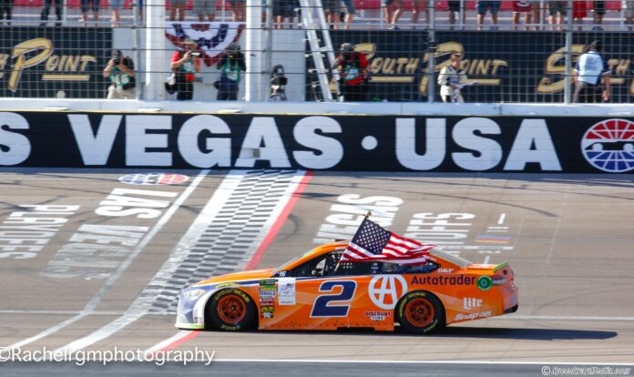 Brad Keselowski does his traditional victory celebration with the American flag. He also celebrated Team Penske's 500th career victory. Photo by Rachel Myers for Speedway Media.