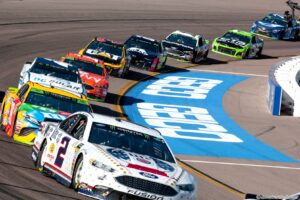 The field races through the new Turns 3 & 4 after one lap taking the green flag for a restart at ISM Raceway. Photo by Rachel Schuoler for Speedway Media.