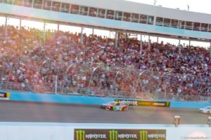 The sun sets behind the grandstands as Kyle Busch pulls away to his 51st career NASCAR Monster Energy Cup Series win. Photo by Rachel Schuoler for Speedway Media.