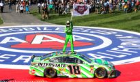 "Kyle Busch waves a ""200 Wins"" flag in celebration of his 200th career victory in NASCAR's premier top touring series. Photo by Rachel Schuoler of Speedway Media."