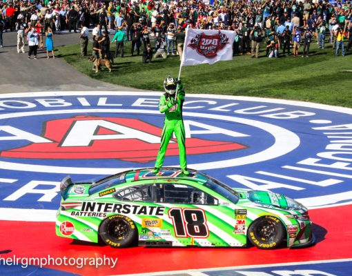 """Kyle Busch waves a """"200 Wins"""" flag in celebration of his 200th career victory in NASCAR's premier top touring series. Photo by Rachel Schuoler of Speedway Media."""
