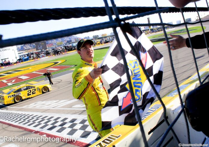 Joey Logano walks the front stretch to grab the checkered flag after winning the Pennzoil 400 at Las Vegas Motor Speedway. Photo by Rachel Schuoler for Speedway Media.
