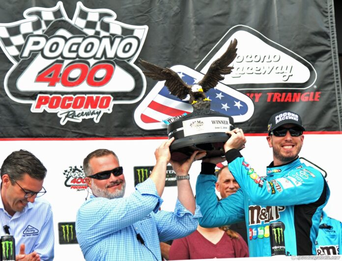 Kyle Busch hoists the trophy after winning the Pocono 400. Photo by Kirk Schroll for Speedway Media.