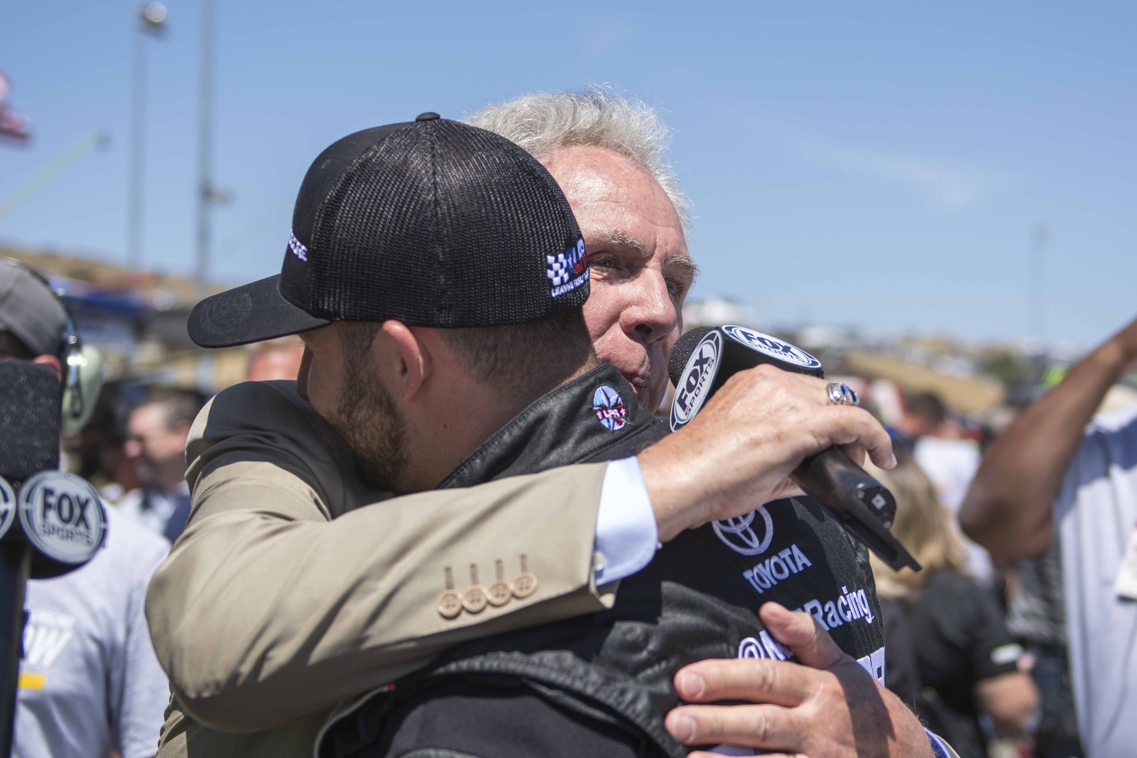 Darrell Waltrip and Matt DiBenedetto share a hug during pre-race ceremonies for Waltrip's final broadcast. Photo courtesy of Patrick Sue-Chan for Speedway Media.