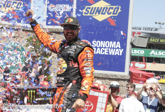 Martin Truex Jr. climbs out of his car in celebration for his third career victory at Sonoma Raceway. Photo courtesy of Rachel Schuoler for Speedway Media.